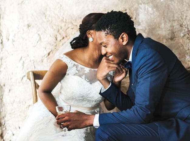Couple de jeunes mariés d'origine africaine s'embrassant