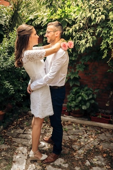 Couple de jeunes mariés se regardant danser danser et souriant le jour de leur mariage. concept d'union et d'amour.