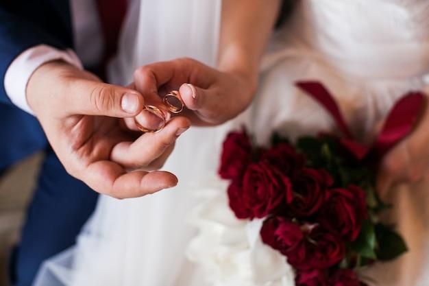 Couple de jeunes mariés tenant dans leurs doigts deux anneaux de mariage. le marié et la mariée montrant une paire d'anneaux de mariée.