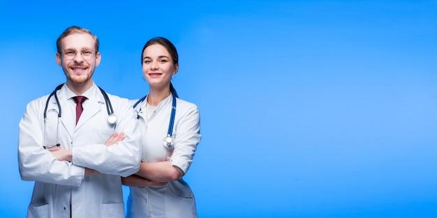 Un couple de jeunes médecins, un gars et une fille, en robes blanches, sourient sur fond bleu. espace libre pour le texte.