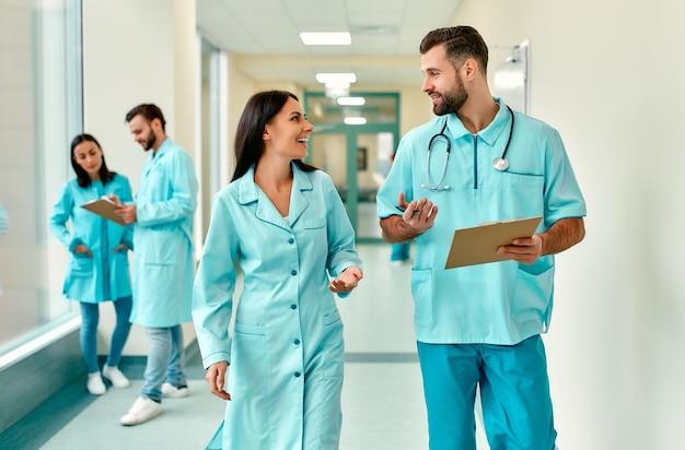 Un couple de jeunes médecins munis d'un stéthoscope et d'une carte de patient se promène dans le couloir de la clinique et discute des méthodes de traitement.