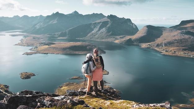 Un couple de jeunes se tenant étreindre au sommet de la montagne