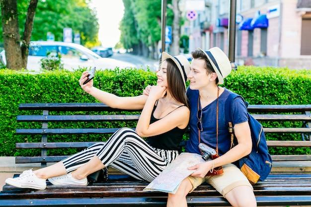 Couple De Jeunes Touristes Sur Un Banc Prenant Un Selfie Photo gratuit