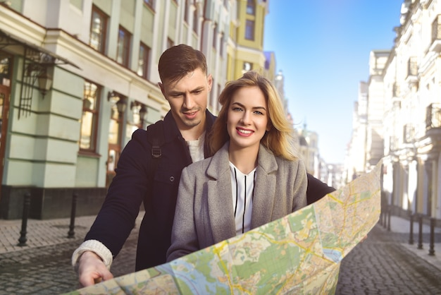 Couple de jeunes touristes lisant une carte dans la ville