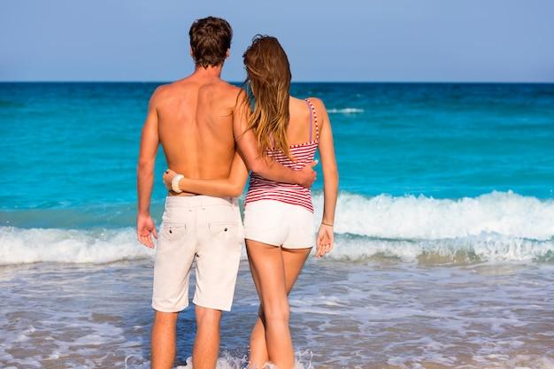 Couple de jeunes touristes sur une plage tropicale