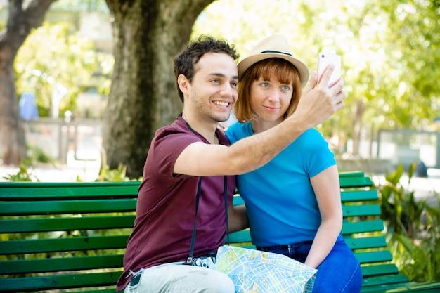 Couple de jeunes touristes prenant selfie avec un téléphone mobile à l'extérieur.
