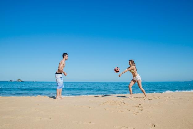Couple jouant au beach-volley au rivage
