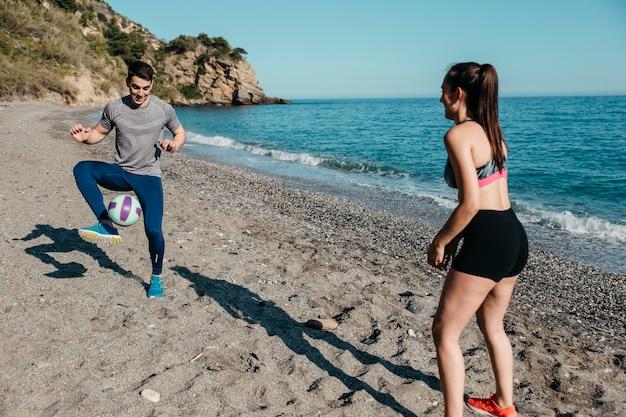 Couple jouant au football à la plage