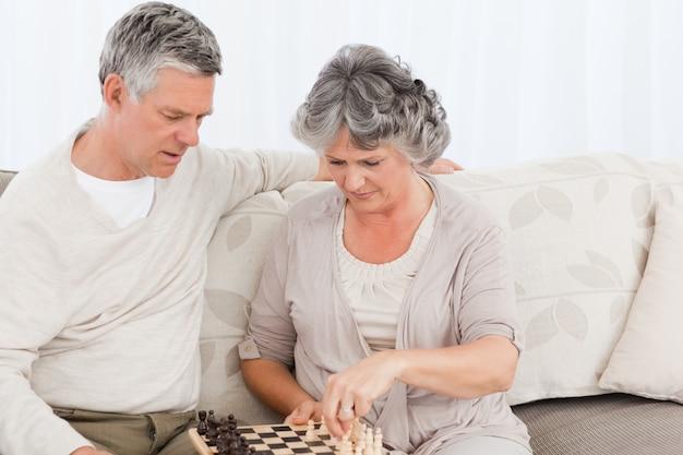 Couple jouant aux échecs sur leur canapé