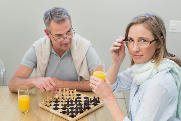Couple jouant aux échecs tout en ayant le jus d'orange