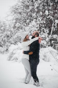 Couple jouant avec de la neige dans la forêt.