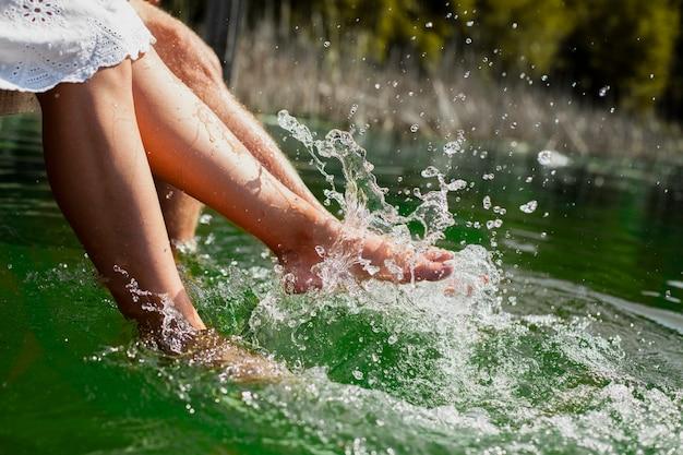 Couple jouant avec les pieds dans l'eau
