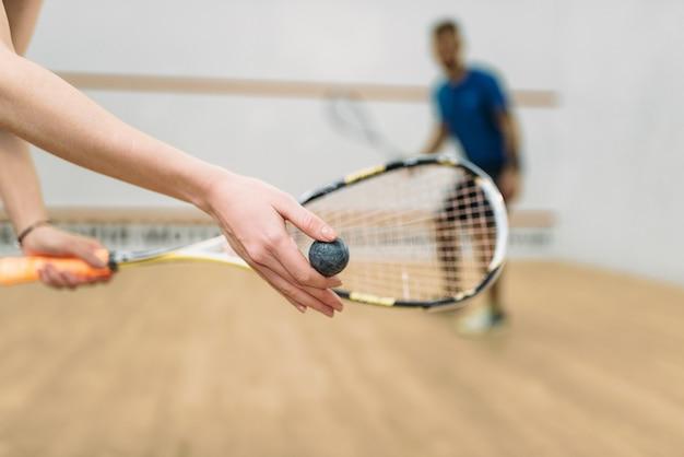 Couple jouer au squash dans un club d'entraînement en salle