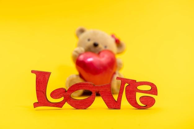 Couple de jouets d'ours en peluche et le mot amour de lettres en bois, coeurs rouges. concept de la saint-valentin. modèle de carte postale.