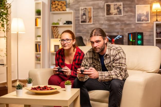 Couple de joueurs jouant à des jeux vidéo sur le téléviseur avec des contrôleurs sans fil dans les mains.