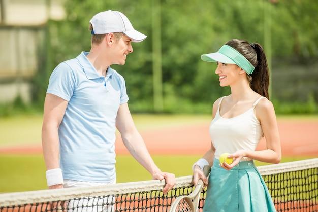Couple de joueurs de tennis discutant sur le court après un match