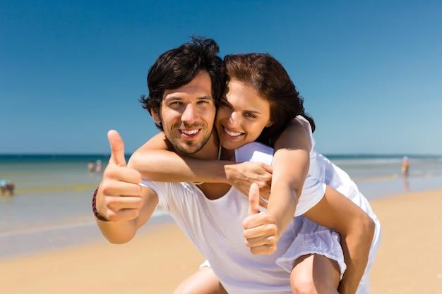 Couple jouissant de la liberté sur la plage