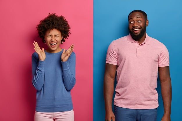 Un couple joyeux s'amuse, rit en regardant un film hilarant, apprécie la comédie, une femme bouclée ne peut pas arrêter de rire, levez les paumes