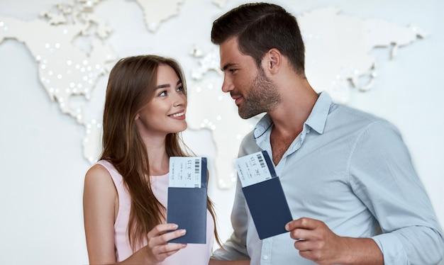 Couple joyeux se regardant et tenant un passeport avec des billets d'avion