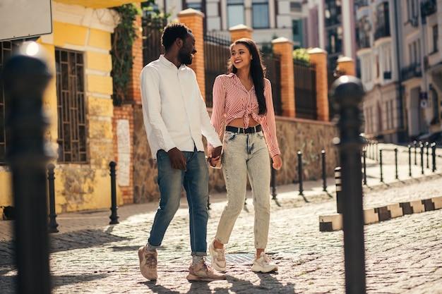 Couple joyeux se tenant la main et se souriant en traversant la rue