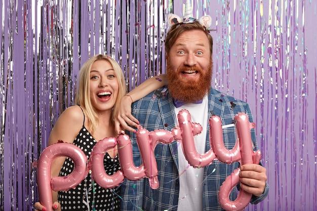 Un couple joyeux se tient côte à côte, s'amuse à l'intérieur, pose dans une photozone décorée