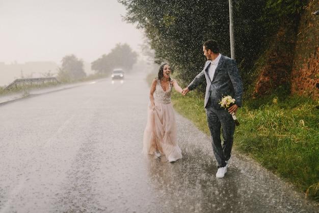Couple juste marié se tenant la main et marchant sous la pluie. marcher dans des vêtements de cérémonie humides sur la route. sourire et s'amuser.