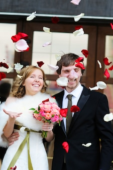 Couple juste marié sous une pluie de pétales de rose