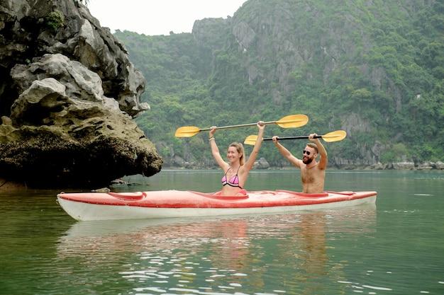 Couple sur kayak célébrant le succès dans la baie d'halong. vue de face sur l'île calcaire avec de l'eau azur de ha long, viet nam.