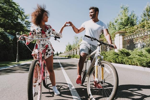 Couple latin va faire du vélo et montrant le coeur de doigt