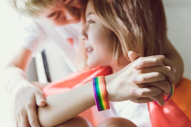 Couple lesbien couvert par le drapeau lgbt et tient son couple par la main.