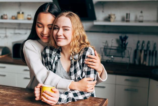 Couple lesbien, étreindre, dans cuisine