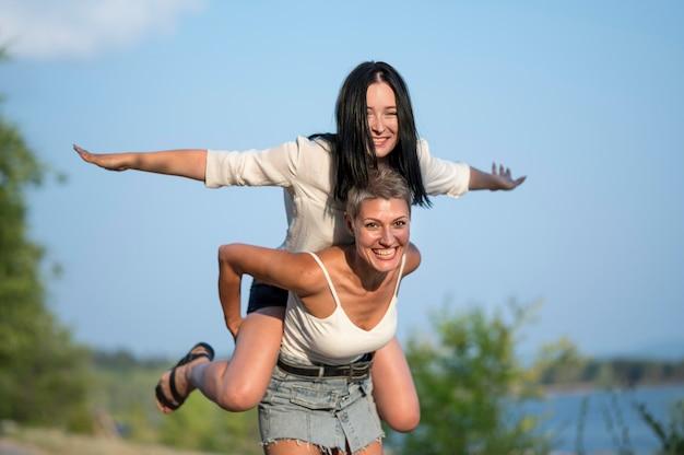 Couple de lesbiennes à angle élevé piggy back ride