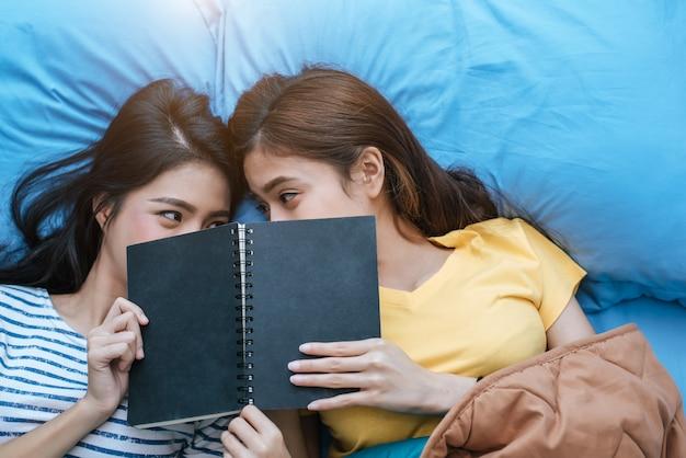 Couple de lesbiennes asiatiques mignons lisant le livre ensemble et couché sur le lit.