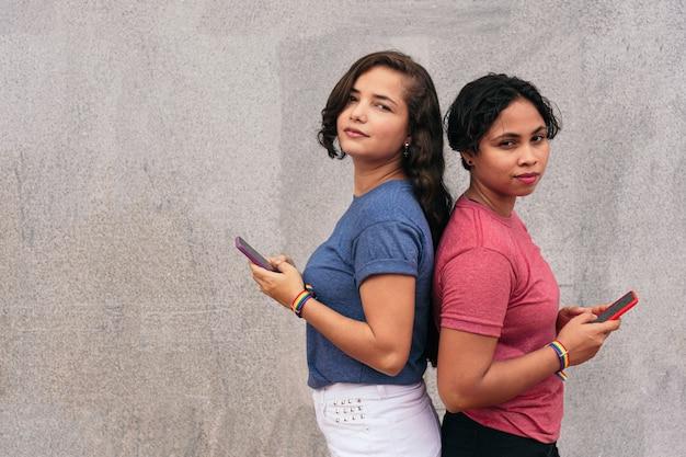 Couple de lesbiennes latines avec téléphone portable dans la rue. notion lgbt