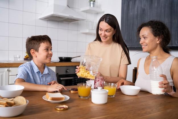 Couple de lesbiennes avec leur fils mangeant le petit déjeuner