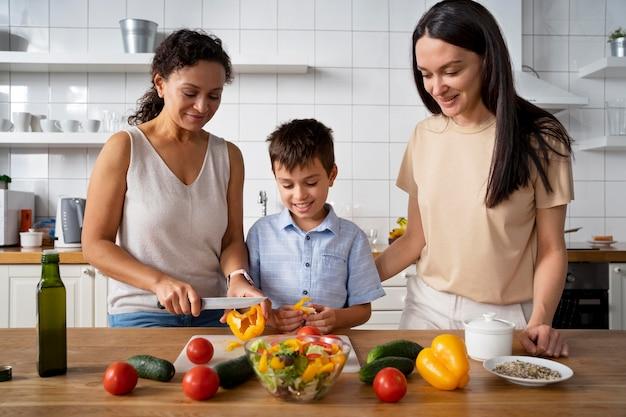 Couple de lesbiennes avec leur fils préparant de la nourriture
