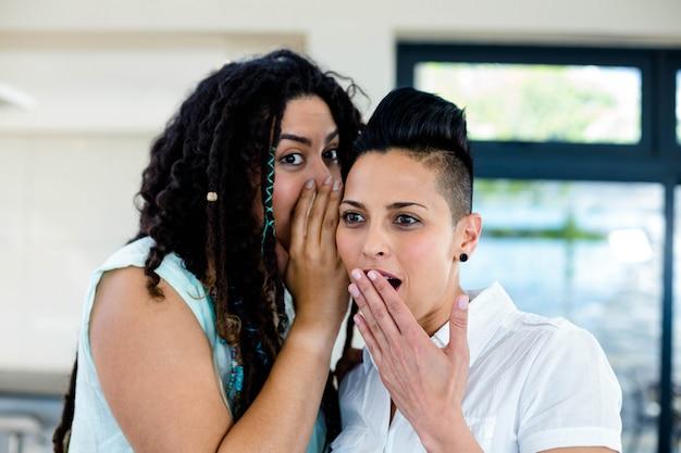 Couple de lesbiennes qui chuchote dans les oreilles et l'air surpris