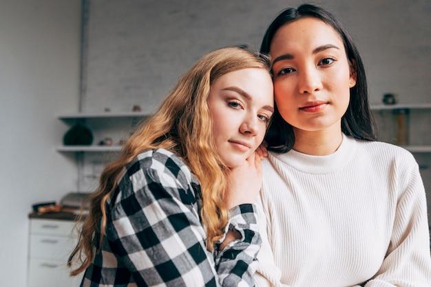 Couple de lesbiennes regardant la caméra à la maison