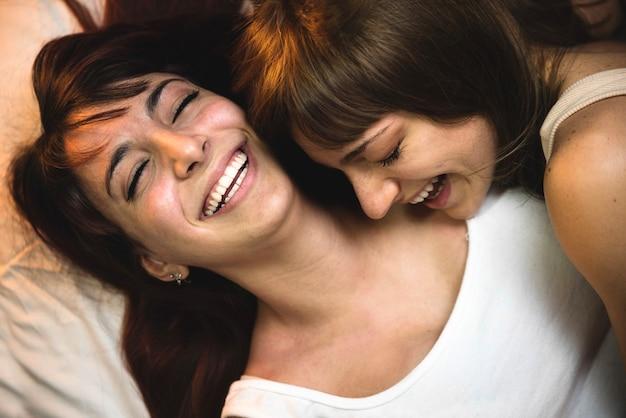 Couple de lesbiennes s'amusant sur le lit - femmes gays ensemble à l'intérieur