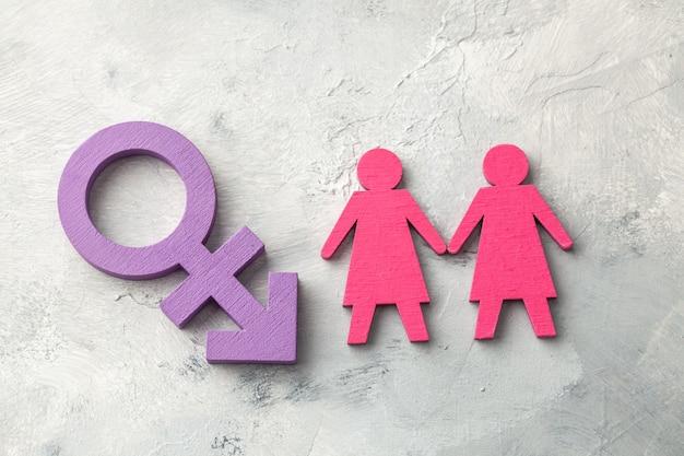 Couple de lesbiennes se tenant la main sur fond de symbole transgenre.
