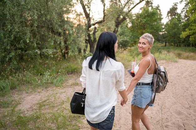 Couple de lesbiennes se tenant la main en plein air