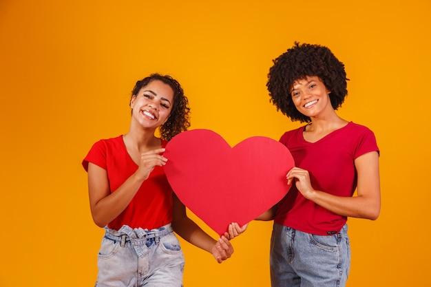 Couple de lesbiennes valentine tenant un coeur en papier. concept de la saint valentin