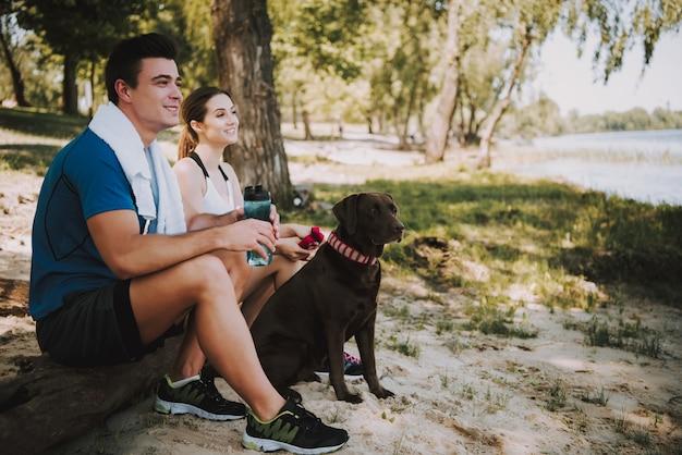 Couple avec leur chien au bord d'une rivière dans un parc
