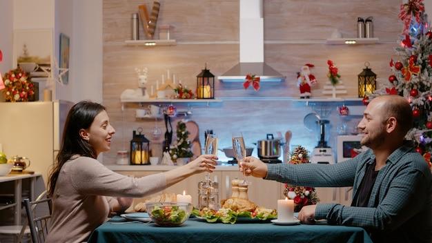Couple levant des verres de champagne célébrant le réveillon de noël