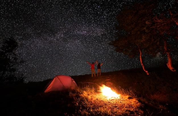 Le couple a levé les mains sous le ciel étoilé brillant parsemé d'étoiles de fées