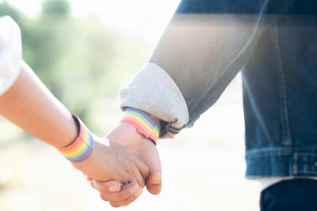 Couple de lgbt se tenant la main marchant dans le parc.