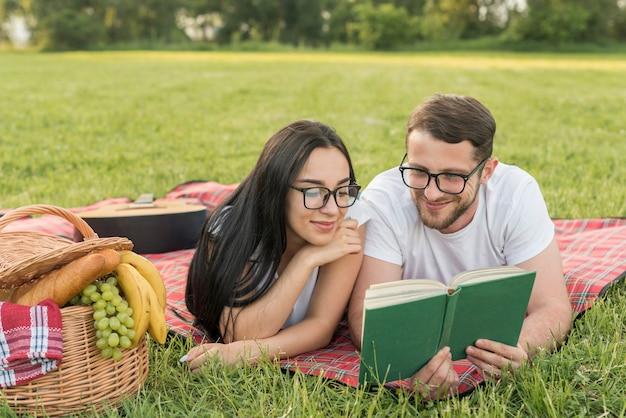 Couple lisant sur une couverture de pique-nique