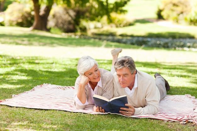 Couple lisant un livre dans le parc