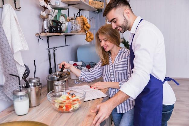 Couple lisant un livre de recettes et cuisinant