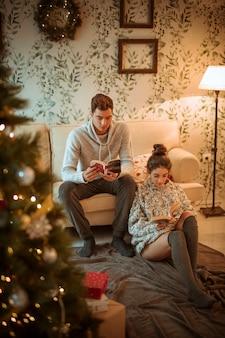 Couple lisant des livres à la maison